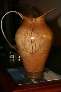 This Jug, or Ewer for those who are more sophisticated, has been turned from Golden Cyprus with brass and copper highlights. The base is Walnut. Wall thickness about 6mm. The handle, which is Jarrah, was cut roughly on the bandsaw and finished with drum sanders and anything else I could get my hands on. It is about 260mm high and was turned when the timber was green which is my preferred option.